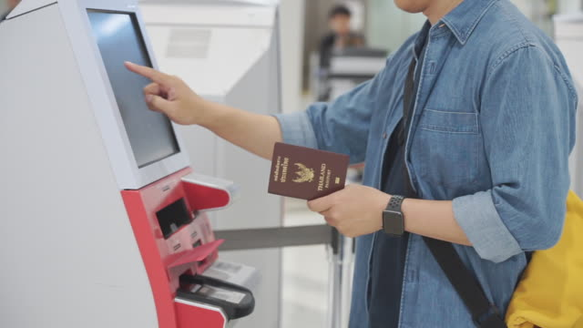 young man touching monitor for using self check-in machine at the airport getting the boarding pass. - kiosk stock videos and b-roll footage