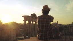 Young man tourist sitting at Roman Forum at sunrise taking picture with vintage camera. Historical imperial Foro Romano from panoramic point of view, Italy