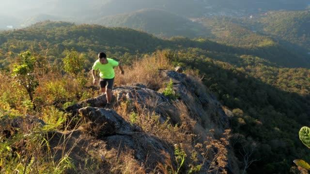 vidéos et rushes de jeune homme coureur de piste en cours d'exécution sur le dessus de la montagne, le mouvement lent - qui monte