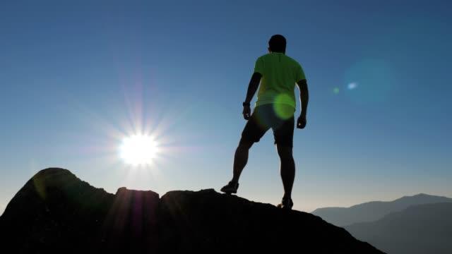 vídeos de stock, filmes e b-roll de corredor de trilha jovem correndo no topo da montanha, câmera lenta - colina acima