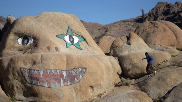 A young man trail running by a boulder with a face painted on it in a mountainous desert. - Slow Motion