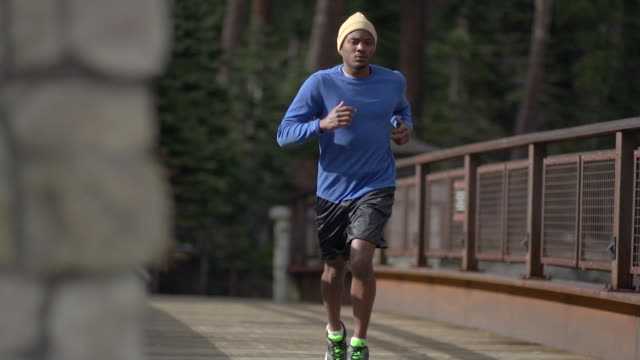 A young man trail running on a bridge at a ski resort hotel in the mountains. - Slow Motion