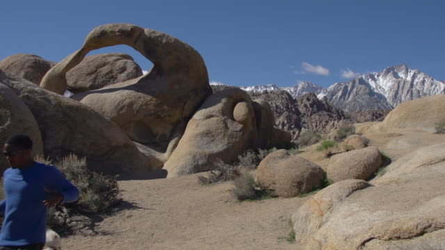 A young man trail running with his dog past a natural rock arch in a mountainous desert.   - Slow Motion