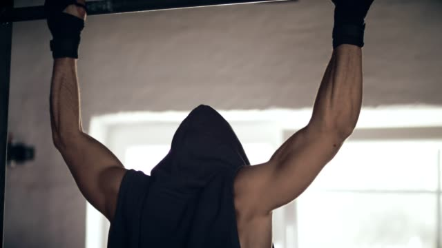 young man training on chin-up bar - chin ups stock videos and b-roll footage