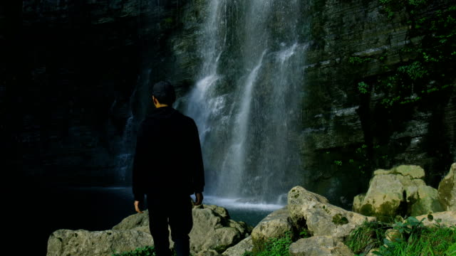 Young man travel by waterfall