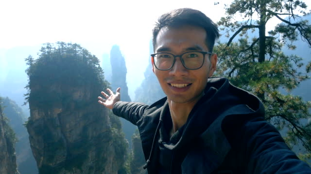 Young man travel in Zhangjiajie National Forest Park,takes selfie