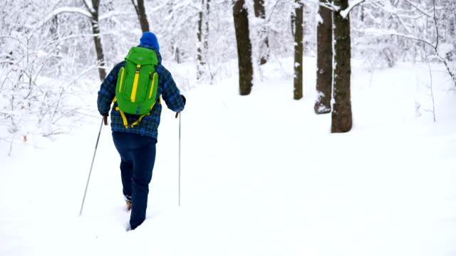 Young Man Traveler walking alone through the snow mountains.