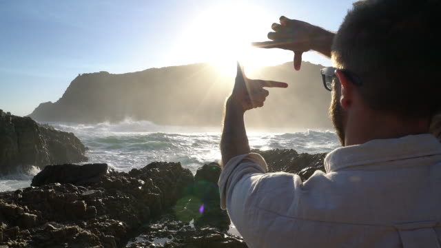 Young man traveling frames sunset with hands