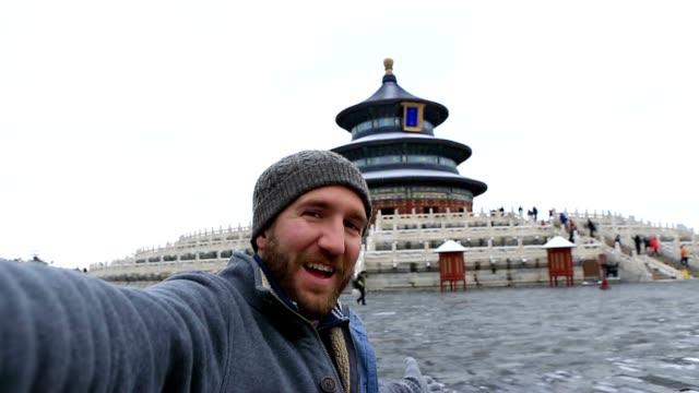 junger mann reisen nimmt selfie mit himmelstempel, beijing - rucksack stock-videos und b-roll-filmmaterial