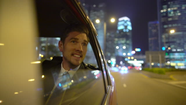 ms ts young man travelling in a car at night, hong kong - geschäftsreise stock-videos und b-roll-filmmaterial