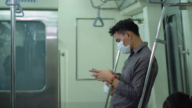 young man travelling in metro train using mobile phone - public transport stock videos & royalty-free footage
