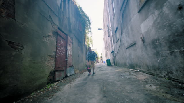 vidéos et rushes de young man tries out new skateboard in urban alleyway - aller tranquillement