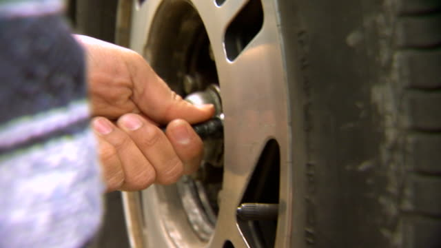 young man turning a lug nut on a tire rim, handheld shot - lug wrench stock videos and b-roll footage