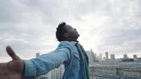 ung man vrida på taket med öppna armar. - framgång bildbanksvideor och videomaterial från bakom kulisserna
