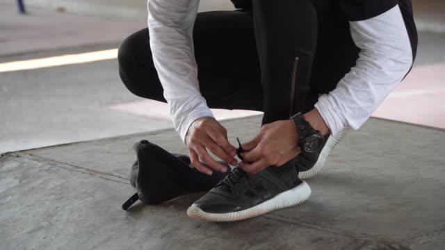 vídeos y material grabado en eventos de stock de un joven atada de encaje de zapatos - reloj de pulsera