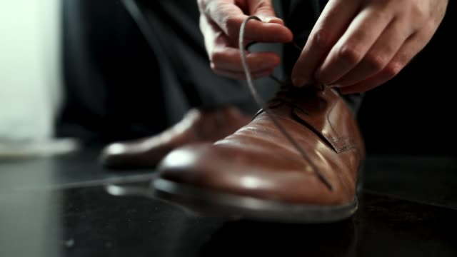 vídeos de stock e filmes b-roll de young man tying shoe laces close-up - castanho