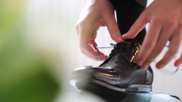 young man tying shoelaces and preparing for wedding - menswear stock videos & royalty-free footage