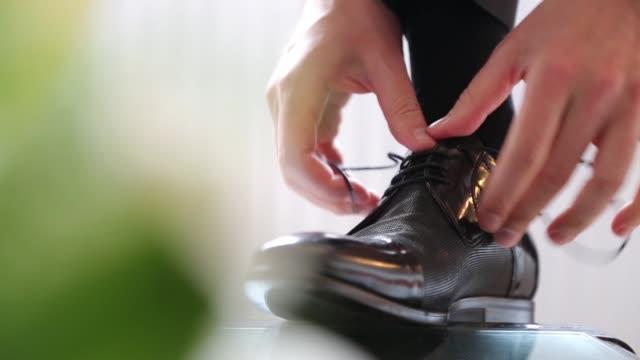 若い男は靴ひもを結び、結婚式の準備をする - 既製服点の映像素材/bロール