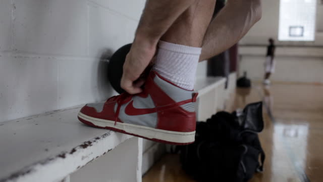 ms young man tying shoe-laces of  his tennis shoes / minneapolis, minnesota, united states  - shoelace stock videos and b-roll footage
