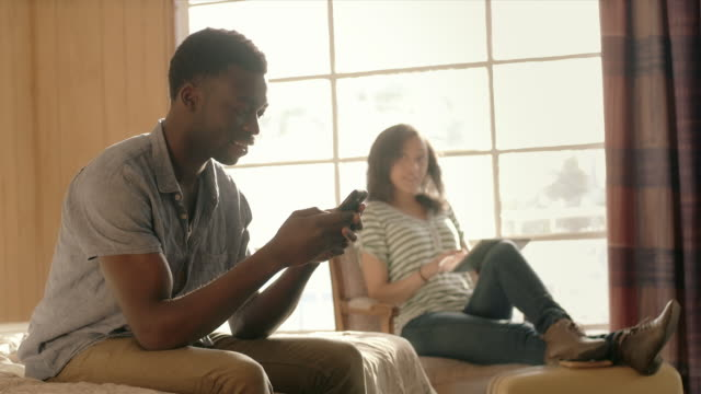 young man types on smartphone while young woman scans tablet - separation stock videos and b-roll footage