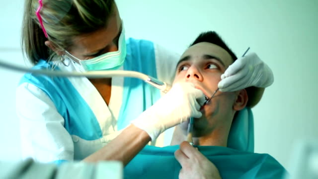 young man under dental procedure. - drill stock videos & royalty-free footage