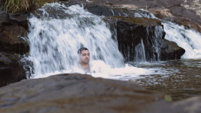A young man under the waterfalls in a river, in Montville, Queensland, Australia