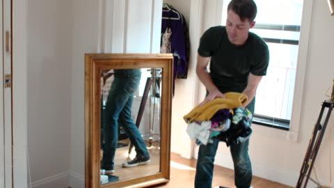 young man unpacks clothes in new apartment - ハイチ点の映像素材/bロール