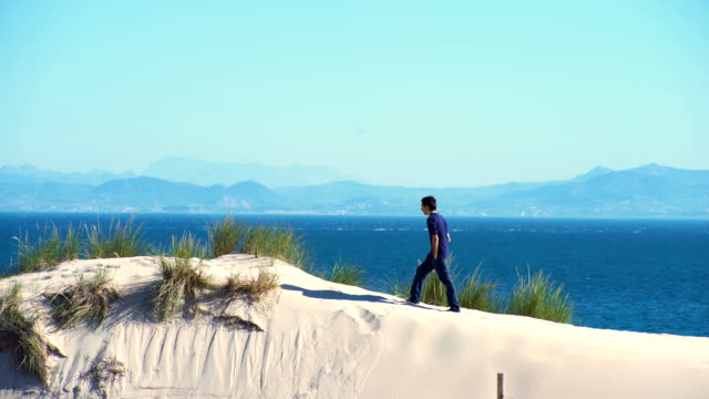a young man upping his arms from a dune sand with ocean and africa coast behind him - one mid adult man only stock videos & royalty-free footage