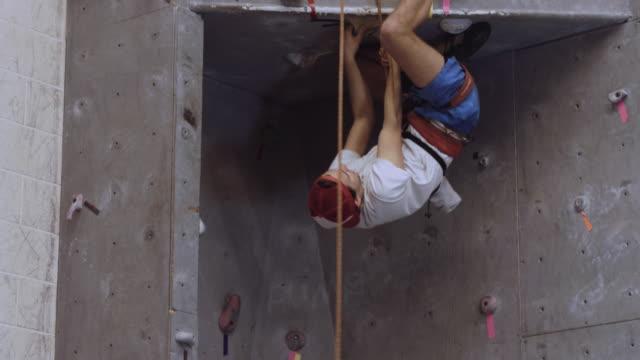 junger mann auf dem kopf stehend auf einem felsen, die route zu klettern - kletterwand kletterausrüstung stock-videos und b-roll-filmmaterial
