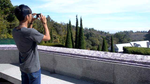junger mann nehmen foto mit telefon - zuschnappen stock-videos und b-roll-filmmaterial