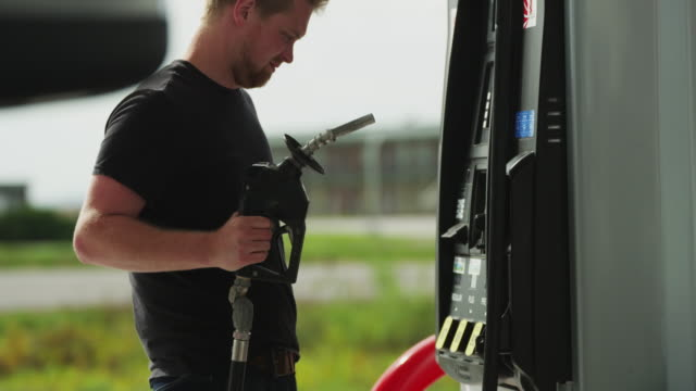 young man uses a credit card at the gas pump of a service station, withdraws the gas nozzle and inserts into a gas tank. - fuel pump stock videos and b-roll footage