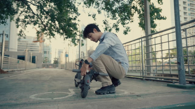 vidéos et rushes de jeune homme utilise un scooter électrique dans les escaliers pour se rendre au travail - monter sur un moyen de transport