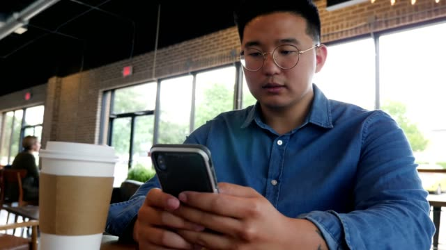 young man uses smartphone in coffee shop - korean ethnicity stock videos & royalty-free footage