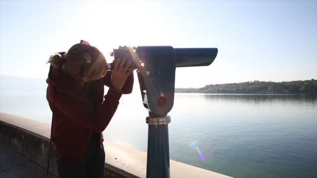 Young man uses spotting scope, looks across calm lake