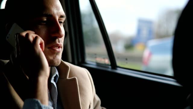 Ung man använder den smarta telefonen i bilen
