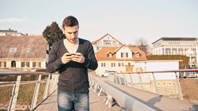 MS TS Young Man Using A Cell On The Bridge