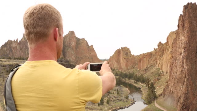 A young man using a cell phone to take a picture inside of Smith Rock State Park.