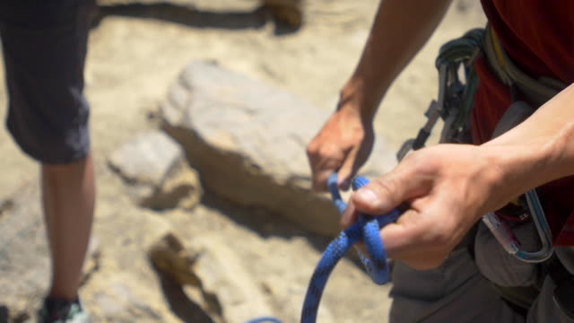 a young man using a figure eight follow-through knot to tie his rope to his harness while rock climbing.  - slow motion - climbing rope stock videos & royalty-free footage