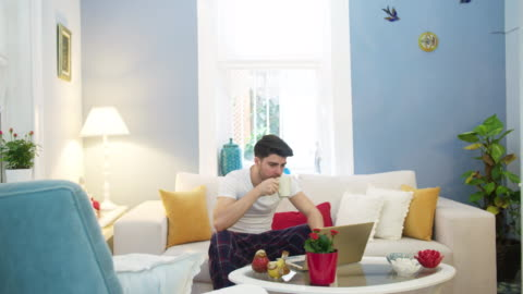young man using a laptop in the living room - pajamas stock videos & royalty-free footage