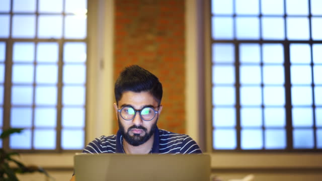 young man using a laptop, reflection of a website in his glasses, close up - programmer stock videos & royalty-free footage