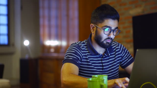 young man using a laptop, reflection of a website in his glasses, close up - studente universitario video stock e b–roll