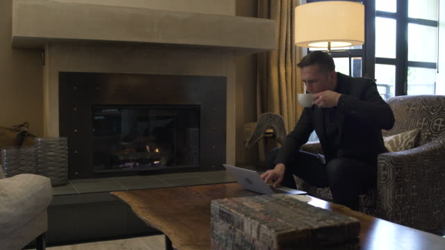 vídeos de stock e filmes b-roll de young man using a laptop while sitting in a suite - lareira