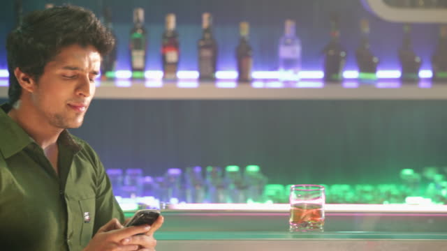 Young man using a mobile phone at bar counter