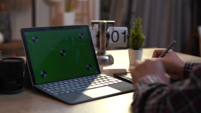 vidéos et rushes de young man using a pen with a digital graphic tablet - graphisme