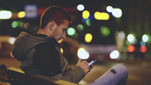 vidéos et rushes de mme young man à l'aide d'un smartphone sur gare routière - banc