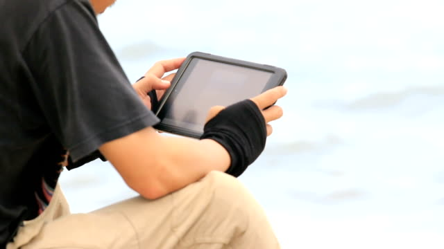young man using a tablet pc outdoors on the beach - patio stock videos & royalty-free footage
