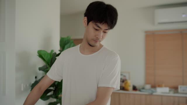 リビングルームで掃除機を使用して若い男 - 掃除機点の映像素材/bロール
