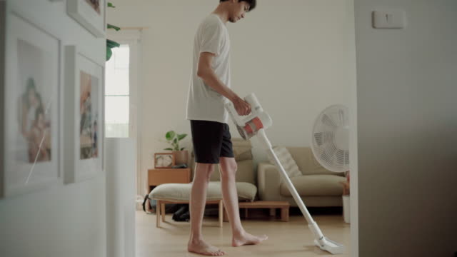 young man using a vacuum cleaner at living room - vacuum cleaner stock videos & royalty-free footage
