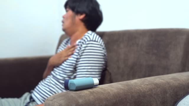 vidéos et rushes de jeune homme utilisant l'inhalateur d'asthme dans la chambre à coucher - inhalateur