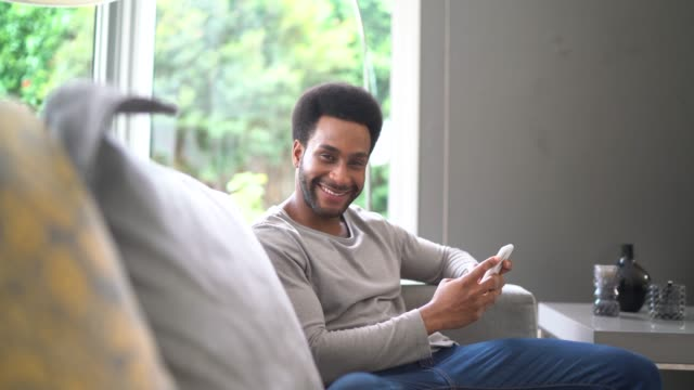 vidéos et rushes de jeune homme utilisant le téléphone portable dans le salon - satisfaction